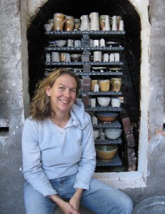 Anne in front of kiln. Anne Goldberg Pottery. Hand made pottery. Carbondale, CO.